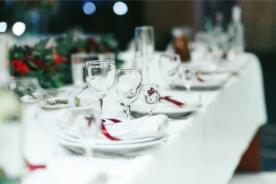 Wedding table set with white napkins and red ribbons